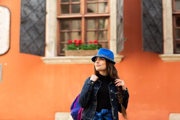 Belle fille souriante au chapeau bleu pose près de la vieille maison rouge