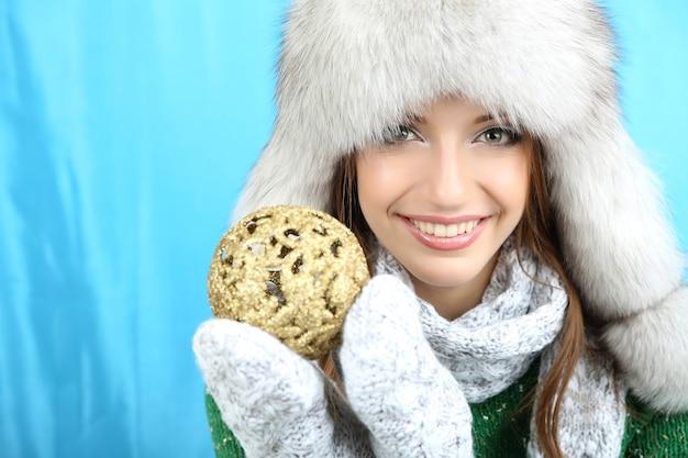 Belle fille souriante avec boule de noël sur fond bleu
