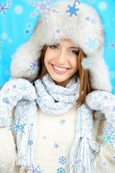 Belle fille souriante en chapeau et mitaines sur fond bleu