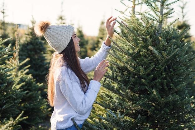 Belle fille souriante choisit un arbre de noël dans une plantation avant les vacances d'hiver.