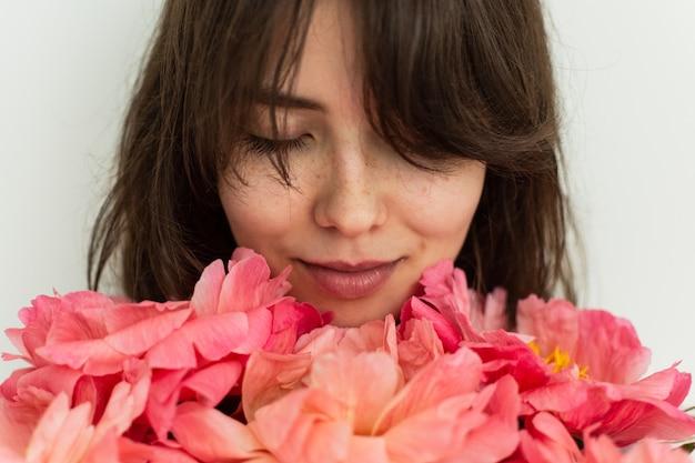 Belle fille souriante du bonheur le jour de son anniversaire, elle tient des pivoines roses contre un mur blanc