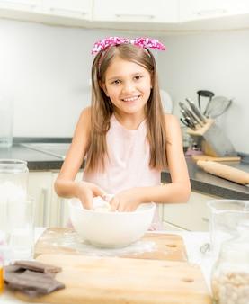 Belle fille souriante faisant de la pâte à tarte dans un bol blanc