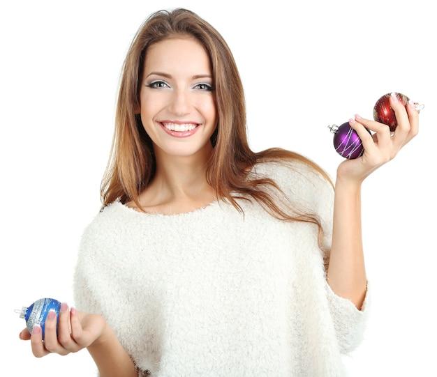 Belle fille souriante avec des jouets de noël isolés sur blanc