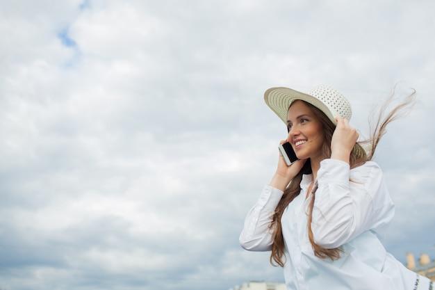 Belle fille souriante parlant au téléphone.
