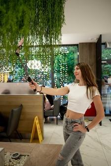 Une belle fille souriante prend un selfie sur son téléphone avec un bâton de selfie dans un centre commercial ou un café.
