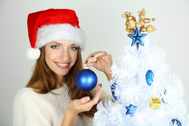 Belle fille souriante près de l'arbre de noël avec ballon