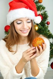 Belle fille souriante près de l'arbre de noël dans la chambre