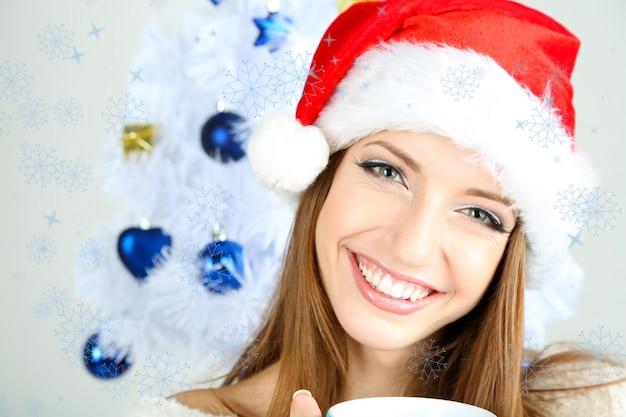 Belle fille souriante près de sapin de noël avec tasse