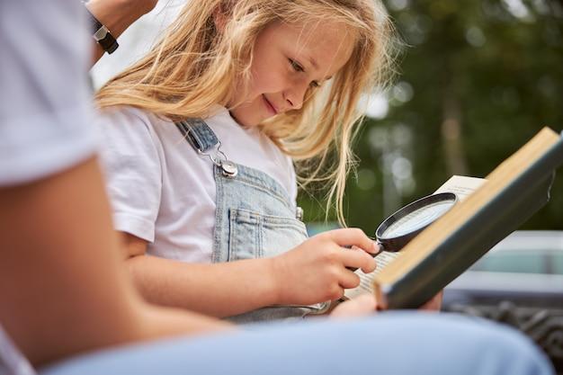 Belle fille souriante regardant à travers le livre tout en utilisant une loupe