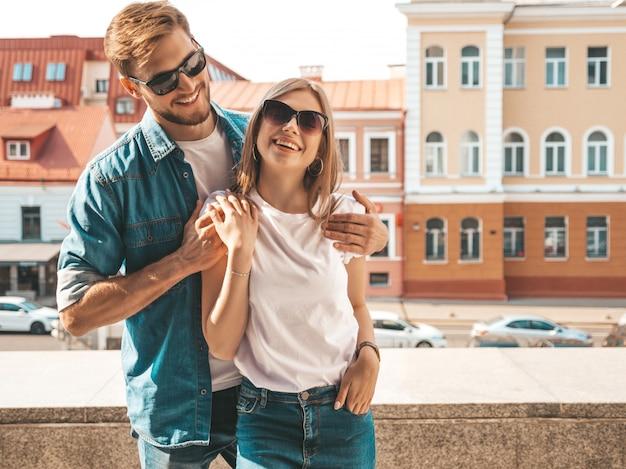 Belle fille souriante et son beau petit ami. femme en vêtements de jeans d'été décontracté. se regarder les uns les autres
