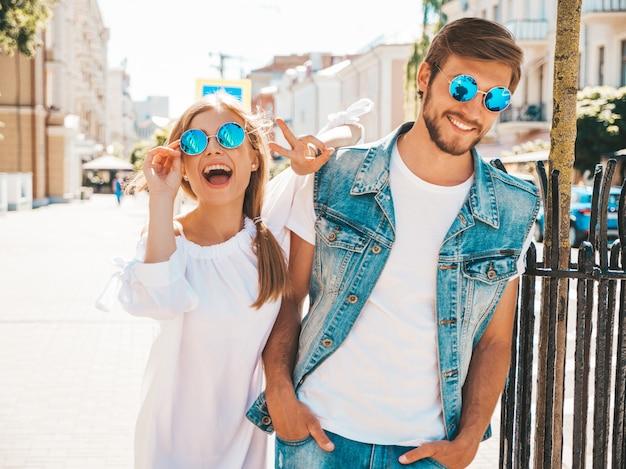 Belle fille souriante et son beau petit ami marchant dans la rue.