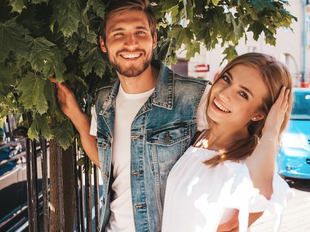 Belle fille souriante et son beau petit ami posant dans la rue près de l'arbre.