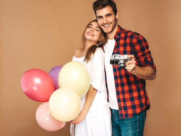 Belle fille souriante et son beau petit ami tenant des tas de ballons colorés. couple heureux, prendre des photos d'eux-mêmes sur appareil photo rétro. bon anniversaire