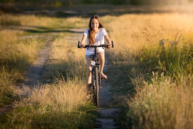 Belle fille souriante à vélo dans les prés au coucher du soleil
