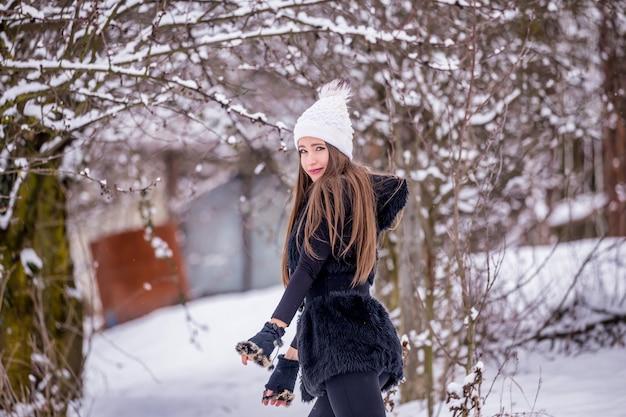 Une belle fille souriante en vêtements noirs et chapeau blanc en hiver