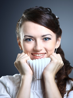 Belle fille sourit dans un pull isolé sur fond gris