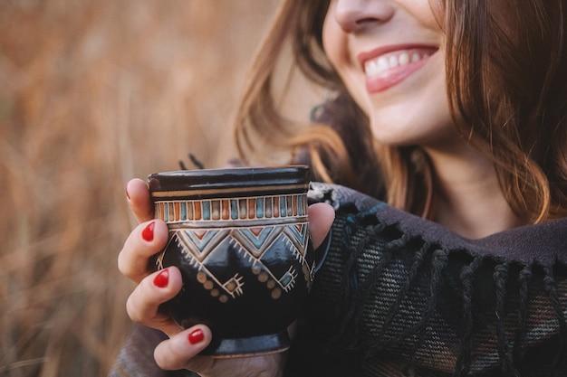 Belle fille sourit et tient une tasse avec un verre. se concentrer sur la tasse.