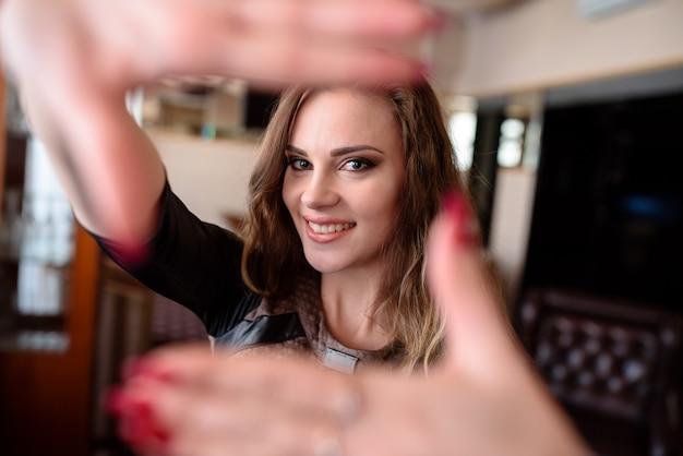 Belle fille sourit et tire les mains vers la caméra.