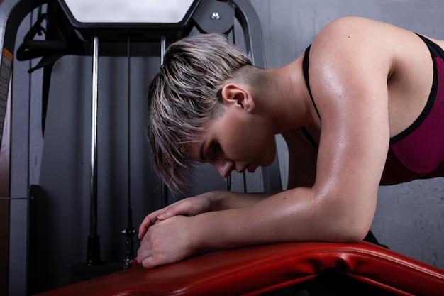 Belle fille de sport est engagée sur un simulateur dans la salle de gym