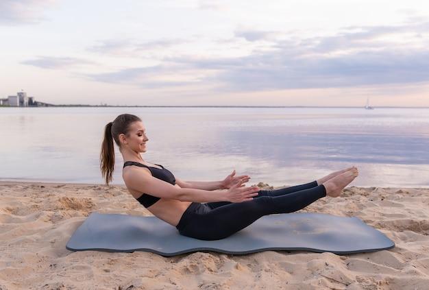 Belle fille de sport secoue la presse au coucher du soleil au bord de la mer