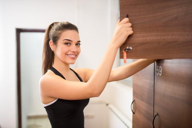 Belle fille sportive au vestiaire du gymnase, souriant à la caméra.