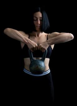 Belle fille sportive aux cheveux noirs surélevée à deux mains avec un poids en métal