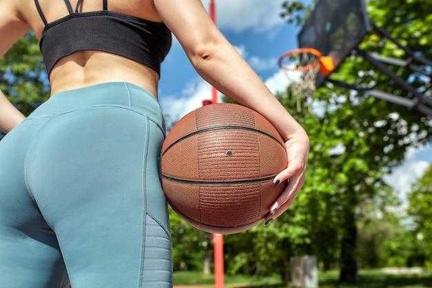 Belle fille sportive avec un ballon de basket sous l'anneau sur un terrain de basket de rue motivation sportive, mode de vie sain