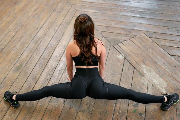 Une belle fille sportive dans un survêtement noir étend la ficelle croisée vue arrière