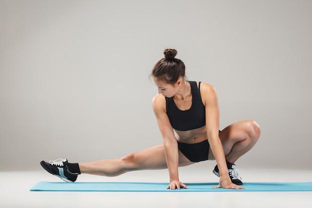 Belle fille sportive debout dans une pose d'acrobate ou yoga asana