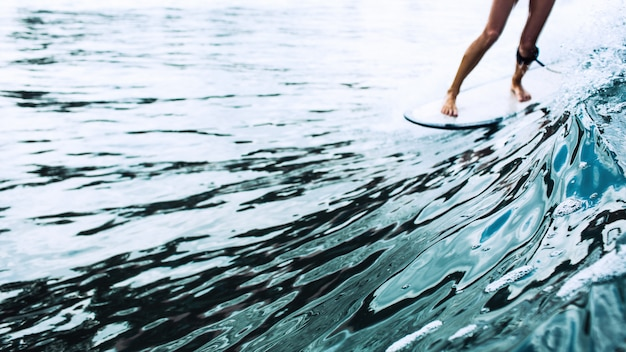 Belle fille de surfeur à cheval sur une planche