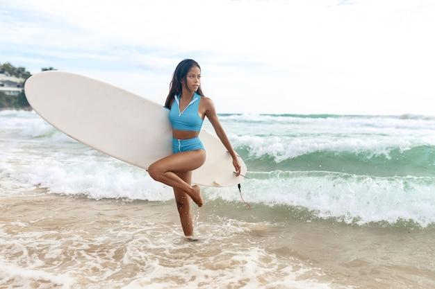 Une belle fille de surfeur avec un corps mince en bikini et avec une planche de surf s'amusant sur la plage.