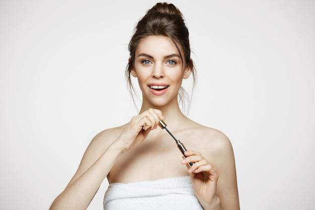 Belle fille surprise avec une peau parfaitement propre regardant la caméra avec la bouche ouverte tenant le mascara sur fond blanc. traitement facial.