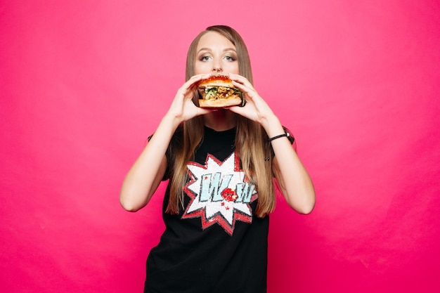 Belle fille en t-shirt manger un hamburger sur rose vif