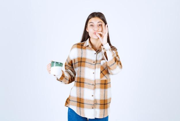 Belle fille avec une tasse de café debout et gesticulant signe délicieux.