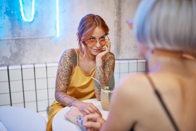 Belle fille tatouée au gingembre dans un café