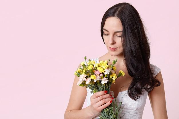 Belle fille tenant un bouquet de fleurs isolé sur rose, femme brune regardant vers le bas sur son présent