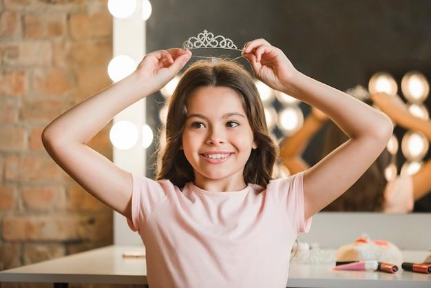 Belle fille tenant une couronne de diamant sur sa tête