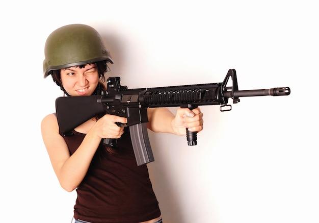 Belle fille tenant un pistolet.