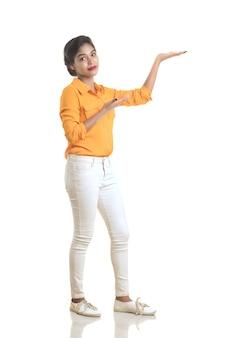 Belle fille tenant et présentant quelque chose dans la main avec un sourire heureux.