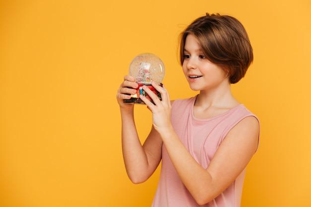 Belle fille tenant et regardant une boule à neige isolée sur jaune