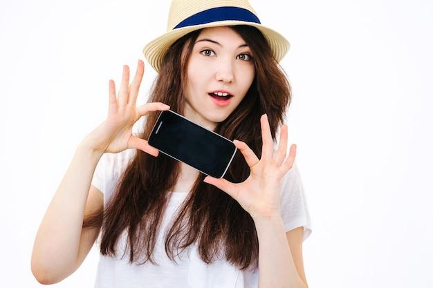 Belle fille tenant un téléphone sur un mur blanc