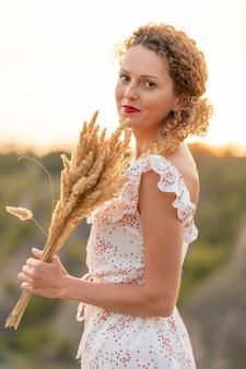 Belle fille tendre dans une robe d'été blanche se promène au coucher du soleil dans un champ avec un bouquet d'épillets.