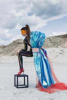 Belle fille en tenue de festival créatif, masque en plastique jaune et snood bleu brillant