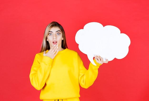 Belle fille en tenue jaune tenant un nuage de discours de nuage de papier