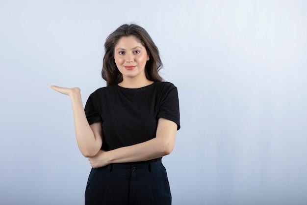 Belle fille en tenue noire posant à la caméra sur un mur blanc.