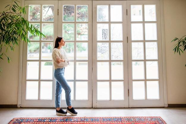 Belle fille sur la terrasse regarde par une grande fenêtre dans un hôtel de charme