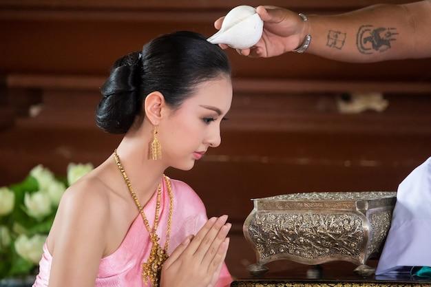 Belle fille thaïlandaise en costume traditionnel à la place du temple thaïlandais