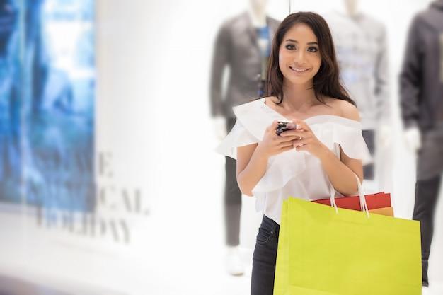 Belle fille tient des sacs à provisions et utilise un téléphone intelligent et souriant tout en faisant des achats