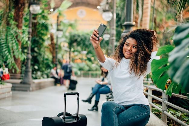 Belle fille touristique prenant selfie.