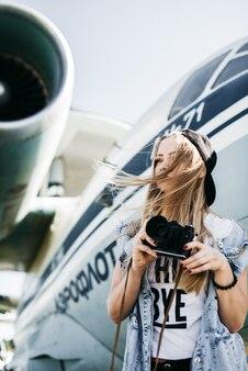 Belle fille touristique avec une vieille caméra vintage de film posant près de l'avion lors d'un jour venteux